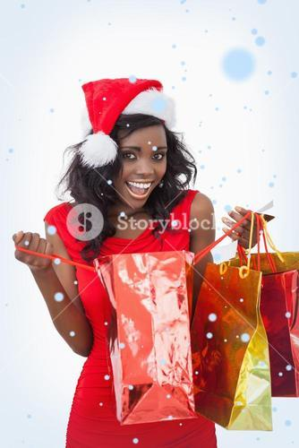 Composite image of woman holding bags while smiling