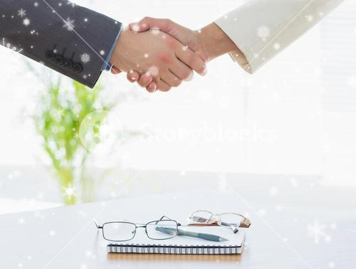 Composite image of shaking hands over eye glasses and diary after business meeting