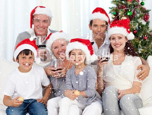 Composite image of family celebrating christmas with wine and sweets