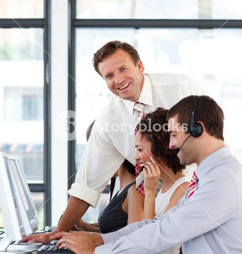 Mature manager in a call center smiling at the camera