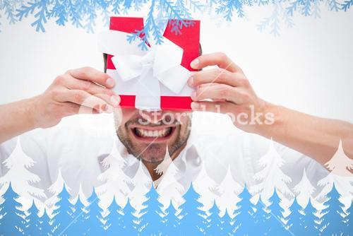 Composite image of stressed man holding a present