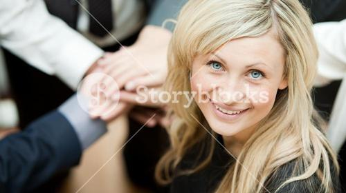 High view of hands together and a businesswoman smiling at the camera. Concept of union in business