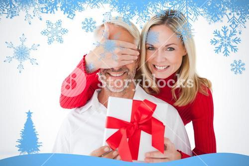 Composite image of smiling woman covering partners eyes and holding gift