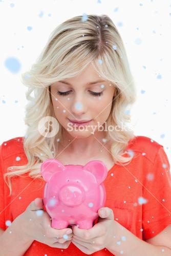Composite image of young woman looking at a piggy bank held by her hands