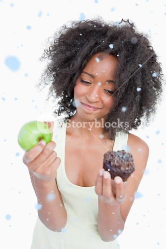 Composite image of young woman hardly hesitating between a muffin and an apple