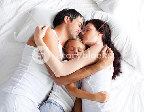Lovely family sleeping on a bed