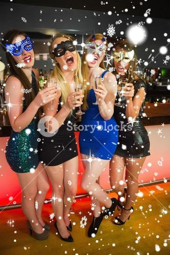 Composite image of laughing friends with masks on holding champagne