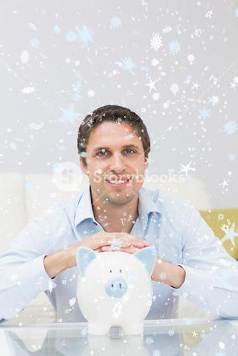 Composite image of handsome casual man with piggy bank in living room