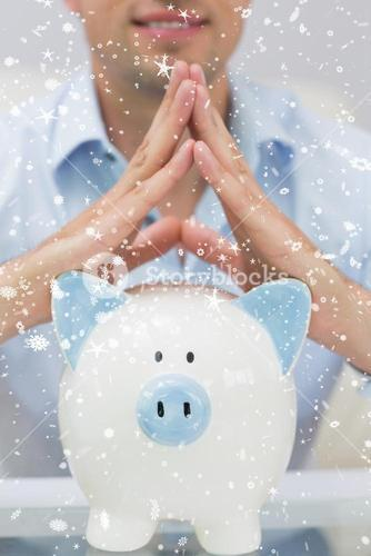 Composite image of closeup mid section man with piggy bank at home