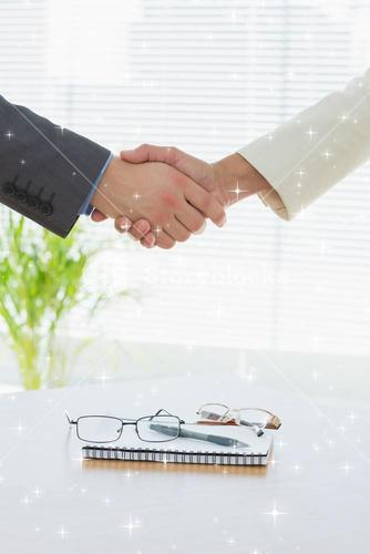 Composite image of closeup of shaking hands over eye glasses and diary