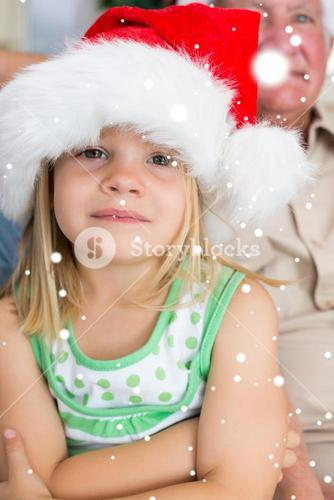 Composite image of girl wearing santa hat at home