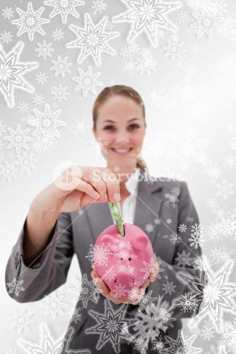 Composite image of money being put into piggy bank by smiling bank employee
