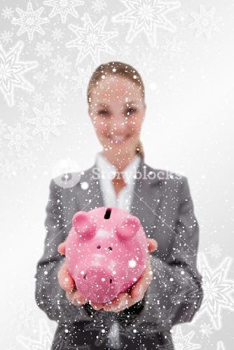 Composite image of piggy bank being held by smiling bank employee