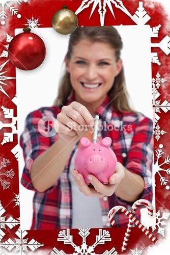 Composite image of portrait of a woman putting a note a piggy bank