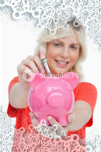 Composite image of young blonde woman putting notes into a pink piggy bank