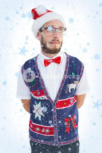 Composite image of geeky hipster in santa hat