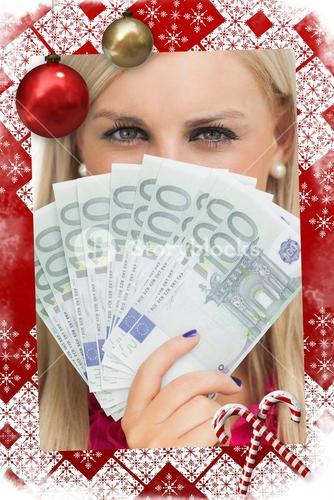 Composite image of green eyed woman holding 100 euros banknotes