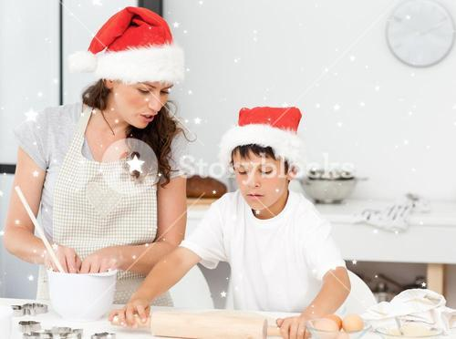 Composite image of mother and son preparing christmas biscuits together
