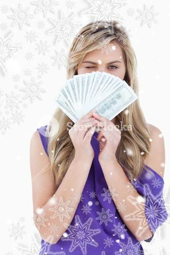 Composite image of blonde woman winking an eye while holding bank notes
