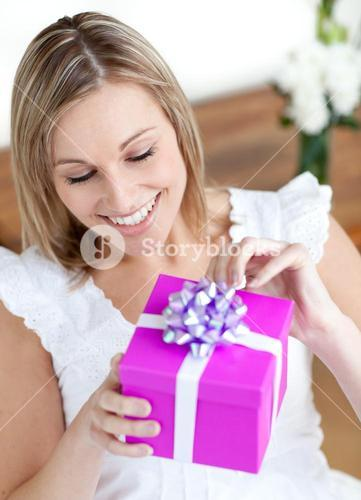 Delighted woman opening a gift sitting on the floor