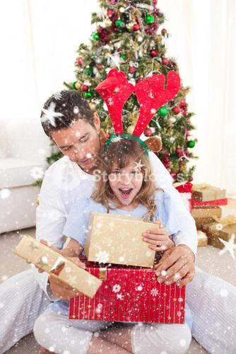Composite image of surprised little girl opening presents with her father
