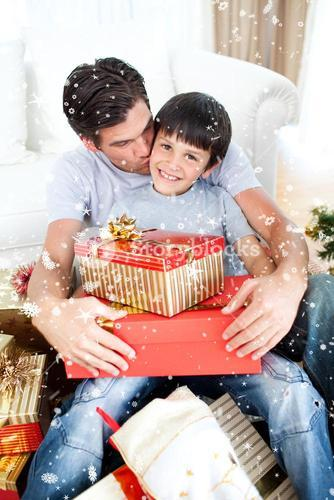 Composite image of father kissing his son after giving him a christmas gift