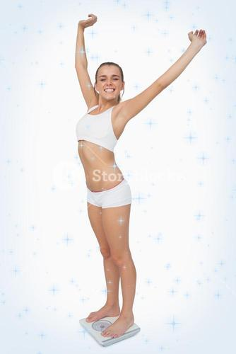 Composite image of happy slim woman standing on a scales spreading her arms