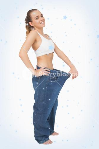 Composite image of cute woman wearing too big blue jeans