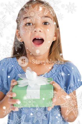 Composite image of excited little girl holding a wrapped gift