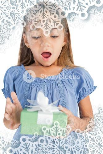 Composite image of surprised little girl holding a wrapped gift