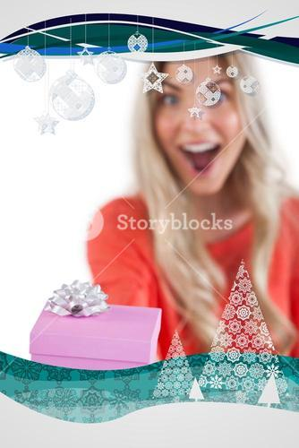 Composite image of astonished woman holding a gift