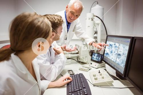 Science students looking at microscopic image on computer with lecturer
