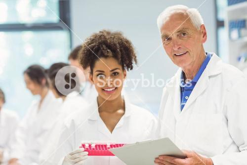 Lecturer and student smiling at camera in the lab