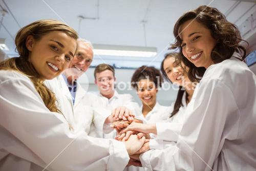 Science students and lecturer putting hands together