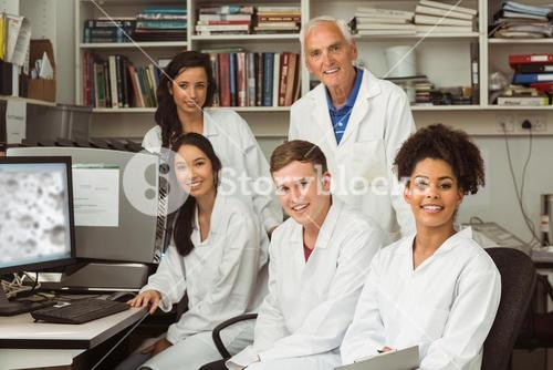 Science students smiling at camera with professor