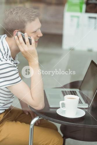 Smiling student using laptop and smartphone in cafe