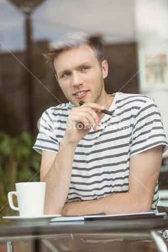 Thinking student sitting with a hot drink and holding a pen