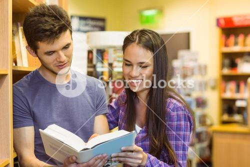 Smiling friends student reading textbook