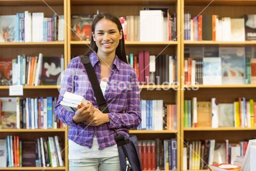 Smiling university student holding textbook