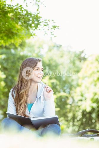 Thinking student sitting and holding book