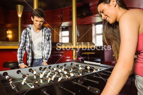 Smiling friends playing table football