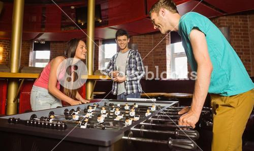 Smiling friends student playing table football in competition