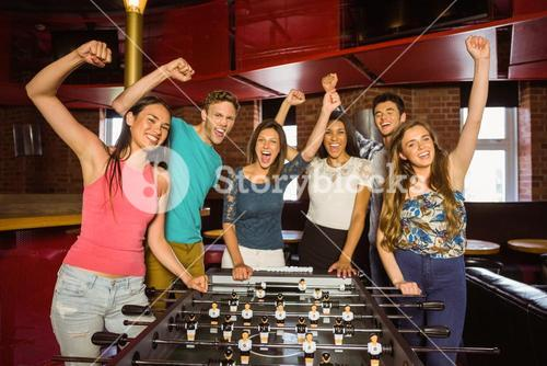 Portrait of happy friends playing table football
