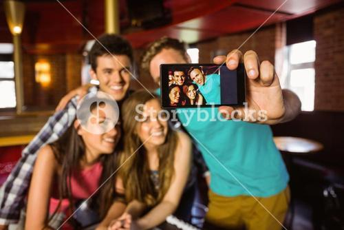 Portrait of happy friends taking a photo with a phone