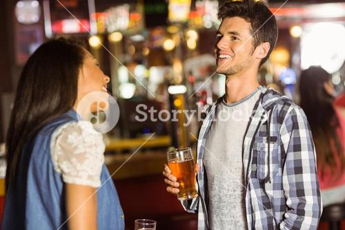 Smiling friends talking and drinking beer and mixed drink