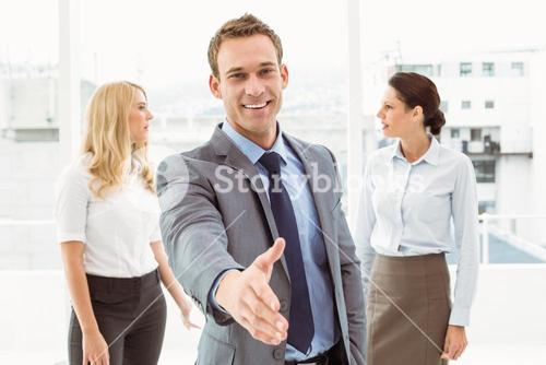 Businessman with colleagues behind at office