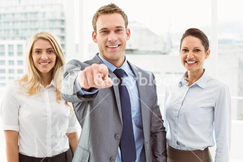 Businessman pointing at you with colleagues in office