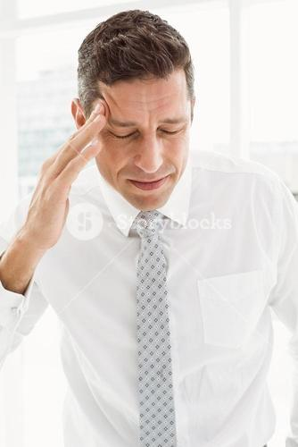 Young businessman with severe headache in office
