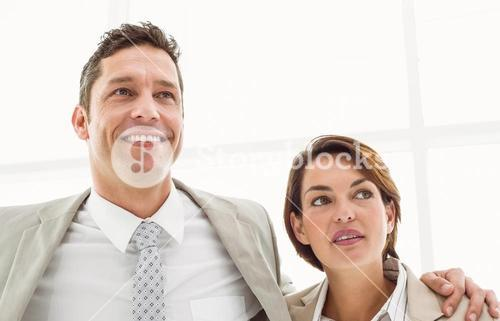 Business couple looking up in office