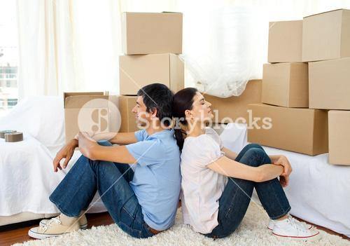 Tired couple relaxing while moving house